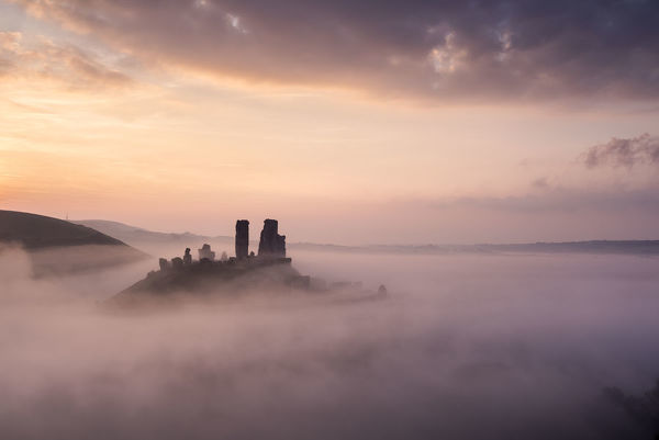 Corfe castle and village at dawn with mist, Corfe Castle, The Purbecks, Dorset, UK. September 2014